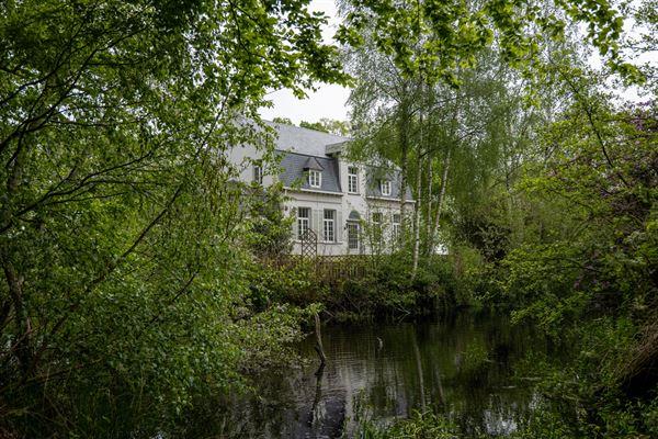 Omgracht kasteel met omliggende bossen engrote tuin, gebouwd op een mottein 1552 . Samen met het neerhof gelegen in een rechthoekige meerv...